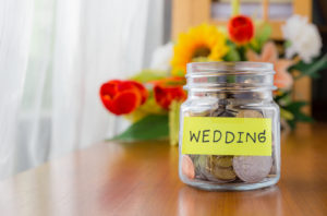 Many world coins in a money jar with wedding label on jar beautiful flowers on background